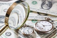 Financez le temps, c'est de l'argent le concept avec de vieux horloges de vintage, billets d'un dollar et loupe Photos libres de droits