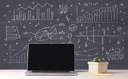 Financiële bedrijfsgrafieken en bureaulaptop Stock Foto's