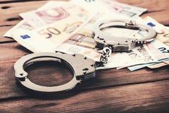 Financiële criminaliteitconcept - geld en handcuffs op de lijst royalty-vrije stock afbeelding