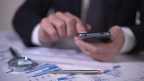 Financiële deskundige die berekeningen op gadget maken, die statistieken in diagrammen bestuderen stock footage