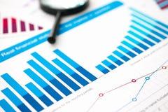 Financiële statistiekendocumenten met lens bij bureaulijst royalty-vrije stock afbeeldingen