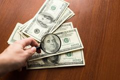 Financiën besparing, belasting of het zoeken naar opbrengstconcept, meer magnifier glas op stapel van dollarbankbiljetten op hout stock foto's