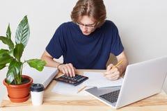 Financiën en betalingenconcept De knappe mens behandelt financiële kwesties, berekent zijn schulden, zit voor geopende laptop, IS Stock Foto