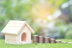 Financiën, Stapel van muntstukkengeld en het Modelhuis die op natuurlijke groene backgroundd, de de sparen voor treffen voortaan  royalty-vrije stock foto's