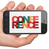 Financiënconcept: Handholding Smartphone met Conferentie over vertoning Royalty-vrije Stock Foto