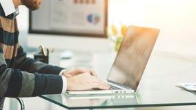 Financiënspecialist die aan laptop met financiële grafieken en marketing regelingen werken stock afbeelding