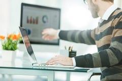 Financiënspecialist die aan laptop met financiële grafieken en marketing regelingen werken royalty-vrije stock afbeelding