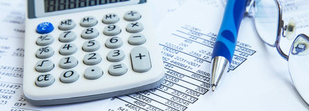 Financial accounting with paper reports and calculator. Financial accounting with tax papers, pen and calculator