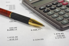Financial accounting with pen and calculator stock images