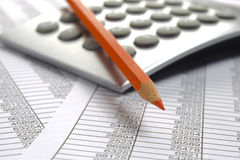 Financial accounting with red pencil and calculator. Financial accounting with table sheet, red pencil and calculator Royalty Free Stock Photography