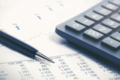Financial accounting stock market graphs analysis. Financial accounting stock market graphs and charts analysis pen and calculator on balance sheets stock images