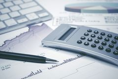 Financial accounting stock market graphs and charts. Financial accounting Pen and calculator on stock market graphs and charts royalty free stock photography