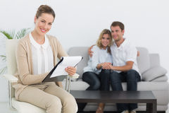 Financial adviser writing notes with couple in background Royalty Free Stock Photos