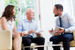 Financial advisor consulting couple in retirement planning. In modern, luminous office stock photo