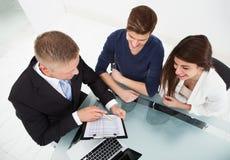 Financial advisor explaining investment plan to couple. High angle view of financial advisor explaining investment plan to couple at office desk Stock Photo