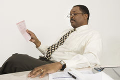 Financial Advisor Reading Document In Office Royalty Free Stock Photos