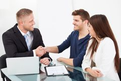 Financial advisor shaking hand with couple Royalty Free Stock Images