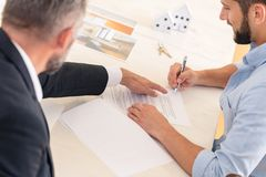 Financial advisor and house buyer. Financial advisor showing buyer where to sign contract to buy house stock images
