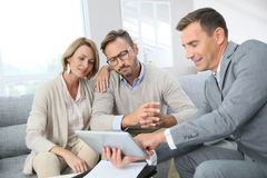 Financial advisor showing contract to clients. Financial adviser showing terms of contract on tablet Royalty Free Stock Images