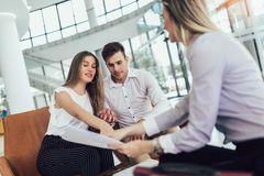 Financial advisor showing report to young couple for their investment. Salesman and positive couple talking about purchase. Happy couple consulting financial royalty free stock photo