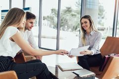 Financial advisor showing report to young couple for their investment. Salesman and positive couple talking about purchase. Happy couple consulting financial stock photography