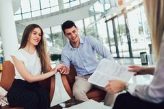 Financial advisor showing report to young couple for their investment. Salesman and positive couple talking about purchase. Happy couple consulting financial royalty free stock images