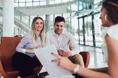 Financial advisor showing report to young couple for their investment. Salesman and positive couple talking about purchase. Happy couple consulting financial stock image