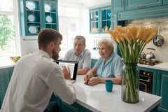 Financial advisor talks with clients. Financial advisor talks with elderly clients in their home. Cozy atmosphere and friendly attitude. Retirement planning stock photos