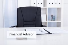 Financial advisor title on nameplate. Photo Of Financial Advisor On Nameplate At Workplace Stock Photo