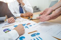 Free Financial Advisory Services. Asian Advisor Showing Plan Of Investment To Clients In The Consultancy Office Royalty Free Stock Images - 198294169