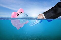 Free Financial Aid And Rescue From Debt Problems For Investments Above Water As A Drowning Pink Piggy Bank Sinking In Blue Water Stock Images - 192014494