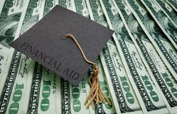 Financial Aid money. Graduation cap with Financial Aid text on assorted hundred dollar bills Stock Photo