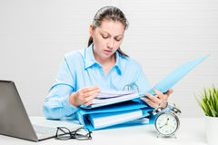 The financial analyst carefully examines. The company`s documents at the desk in the office royalty free stock images