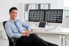 Financial analyst. Portrait of smiling Vietnamese analyst sitting at his workplace stock image