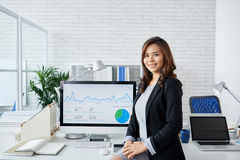 Financial analyst. Portrait of young Asian business woman standing at computer with financial chart on it Stock Image