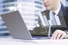 Financial Analyst Reviewing a financial reports. Businessman or analyst looking into a laptop computer notebook deeply reviewing a financial reports for a return stock image