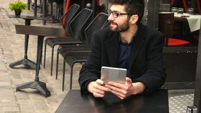 Financial analyst sitting with tablet at cafe table and resting. Skilled financial analyst chatting with tablet at cafe table and smiling. Resting young man stock video footage