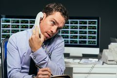 Financial analyst. Talking on the telephone and writing down some information stock photo