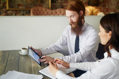 Financial analysts. Bearded trader showing online financial data to co-worker royalty free stock images