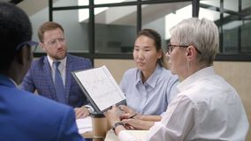 Financial analytic showing report to boss on briefing in office. Multi-ethnic executive people sitting in meeting room discussing strategy stock footage