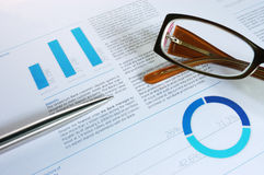 Financial annual. With pen and glasses Stock Image