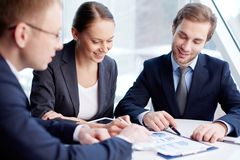 Financial aspects. Positive business people analyzing financial aspects of their work Stock Images