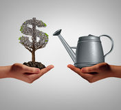 Financial Assistance. And business help concept as two hands holding a watering can and a struggling money tree as a budget aid relief symbol for investing in Stock Photography