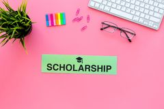 Financial assistance for students. Word scholarship with graduation cap on pink work desk with keyboard top view copy. Financial assistance for students. Word royalty free stock photography