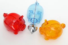 Financial balance. Three colorful piggy banks with metal plumb on white background royalty free stock image