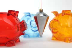 Financial balance. Three colorful piggy banks with metal plumb on white background stock image