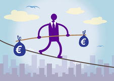 Financial Balancing Euro. A businessman walking on a tightrope over a city, balancing two large bags of Euro money. A metaphor about financial prudence Royalty Free Stock Images