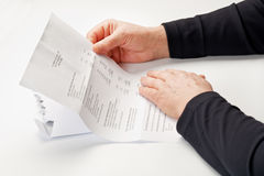 Financial Bill. Elderly female hands holding a financial statement or a detailed business bill Stock Photos