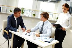 Financial briefing. Office workers discussing financial statistics in office royalty free stock images