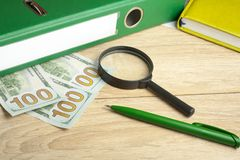 Financial and budget concept. Accounting books, money, magnifying glass and pen on office table Stock Image